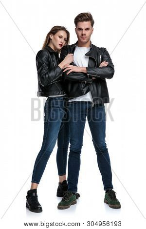Tough guy protecting his girlfriend and standing with his arms crossed at his chest while she is hugging him, both wearing leather jackets and jeans