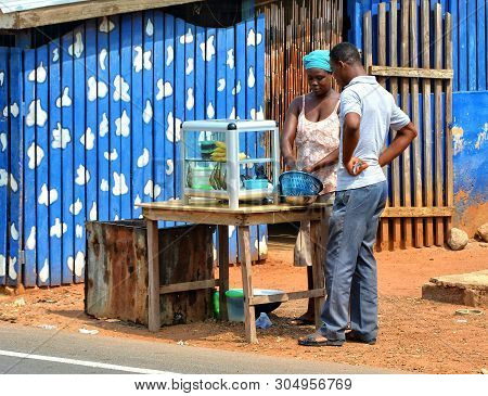 African Street Vendor Sells Local Products. Street Stall With Food In West Africa. Ordinary Street L