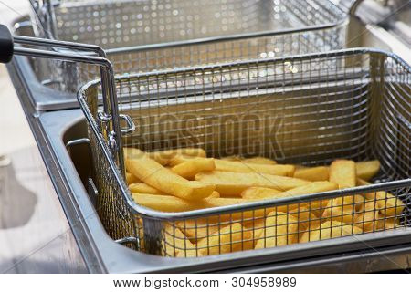 French Fries Cooking. Closeup View Of Making French Fries Deep Frying In An Equipment In Fast Food.