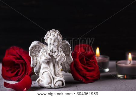 Mourning Concept. Little Angel, Red Roses And Burning Candles On  Dark Background. Card For Mourning