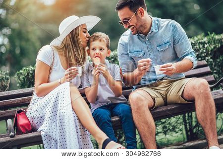 Young Happy Family Spending Their Weekend In The Park. They Are Eating The Ice Cream.