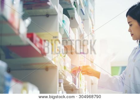 Pharmacist Holds A Packet Of Pills In Her Hands. Then She Shows A Thumbs Up. A Woman Is Standing In