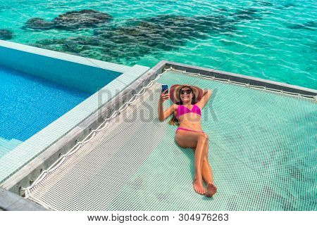 Luxury resort vacation tourist woman relaxing on overwater catamaran net bed in private bungalow suite using phone taking pictures of summer holiday high end hotel.