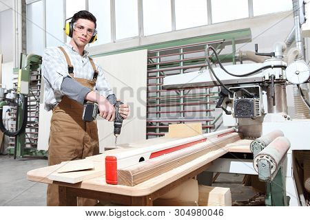 Carpenter Man Work In The Carpentry, With Cordless Drill Driver Screw A Board, Protected With Ear Mu