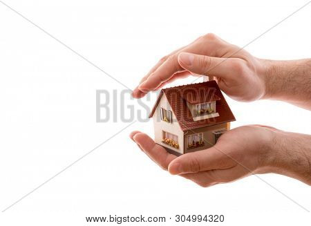 Home protection. Small house covered by hands isolated on white background with clipping path