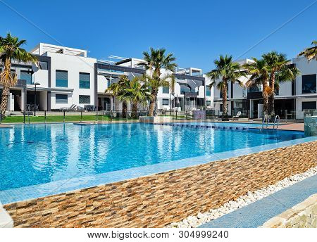 Torrevieja, Spain - May 1, 2019: View To New Built Modern Town Houses Closed Urbanization With Swimm