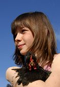 pensive girl and her little little black chicken in a farm (focus on the girl) poster
