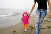 The little girl and mum walk at the sea. On a background a fog.