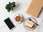 Coffee and cheescake on white marble tabletop. Top view or flat lay. Coffee cup, piece of cheesecake, smartphone, book and succulent. Home office, female workspace concept poster