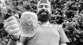 Distinct beer culture. Hipster brutal bearded man hold mug cold fresh beer. Man relaxing enjoying beer in summer. Alcohol drink and bar. Craft beer is young, urban and fashionable. Cheers concept poster