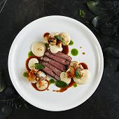Exquisite Serving White Restaurant Plate of Black Angus Beef Fillet with Warm Potatoes in Cheese Sauce and Mushroom Espuma. Luxury Molecular Dish with Sliced Veal Meat on Black Marble Backdrop poster