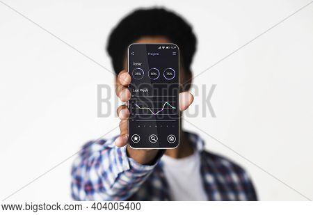 Progress App. Black Guy Demonstrating Smartphone Screen With Project Progress Tracker Standing Posin