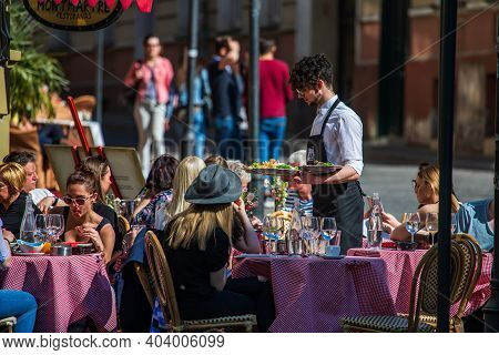 Vilnius, Lithuania - May 14, 2017: People Have A Lunch In A Popular Street Cafe In Didzioji Street O