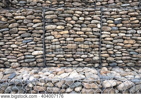 Metal Cage Filled With Rocks Texture . Stone Wall With Metal Grid As Background.  Gabion Net