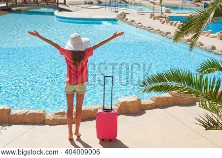 Travel, Summer Holidays And Vacation Concept - Beautiful Woman Raises Her Hands Up Near Hotel Pool A