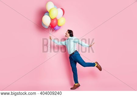 Full Length Profile Photo Portrait Of Man Standing On One Leg Holding Helium Balloons Isolated On Pa