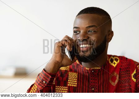 Mobile Call. Smiling African American Guy In Ethnic Shirt Talking On Cellphone, Positive Black Man I