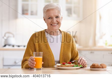 Cheerful Attractive Grandmother In Casual Outfit Posing In Kitchen, Having Healthy Lunch Alone, Copy