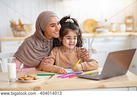 Loving Muslim Mom Helping Her Little Daughter To Study With Laptop At Home, Cute Child And Islamic M