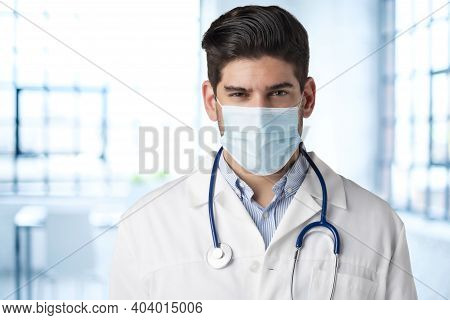 Portrait Shot Of Careworn Male Doctor Wearing Face Mask For Prevention While Standing In Hospital's