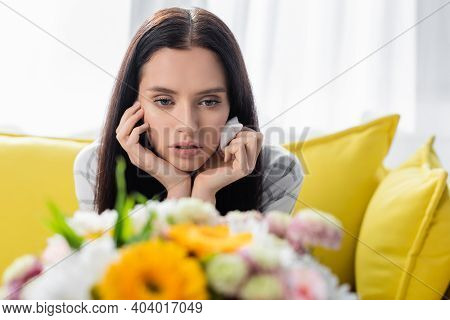 Upset Allergic Woman Holding Paper Napkin Near Flowers On Blurred Foreground