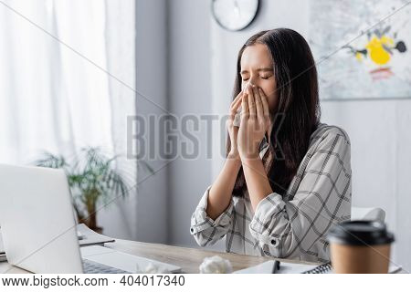 Young Allergic Freelancer Sneezing In Paper Napkin Near Laptop And Coffee To Go On Blurred Foregroun