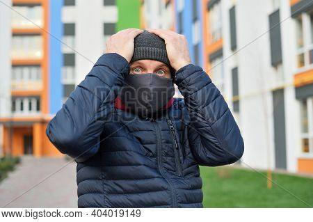 Coronavirus Panic. Man With A Mask On His Face In The City Panic Over The Bad News Concerning Corona