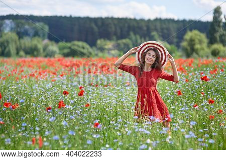 Dreamy Woman In Red Dress And A Big Red Striped Hat In Beautiful Herb Flowering Poppy Field. Vintage