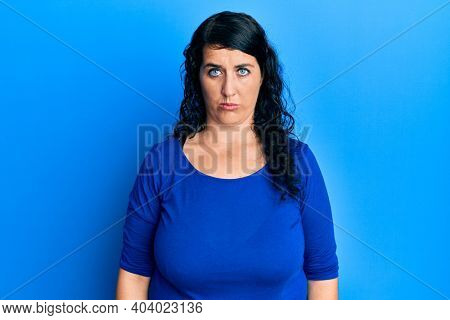 Plus size brunette woman wearing casual blue shirt depressed and worry for distress, crying angry and afraid. sad expression.