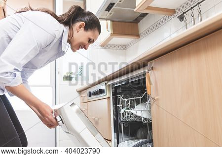 Happy Young Caucasian Woman, Opening The Dishwasher In The Kitchen Of Her Apartment. Housework Conce
