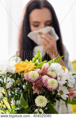 Selective Focus Of Bouquet Near Allergic Woman Wiping Nose With Paper Napkin On Blurred Background
