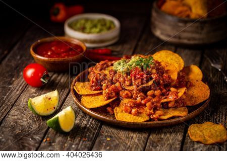 Delicious Plate Of Yellow Corn Nachos Chips With Cheese, Minced Meat And Red Hot Salsa Over Wooden T