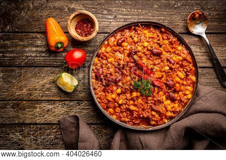 Mexican Hot Chili Con Carne In A Bowl With Tortilla Chips On Dark Background, Top View