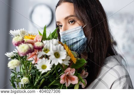 Young Allergic Woman In Medical Mask Holding Bouquet Of Flowers At Home