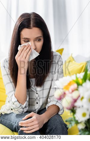 Allergic Woman Wiping Tears Near Flowers On Blurred Foreground