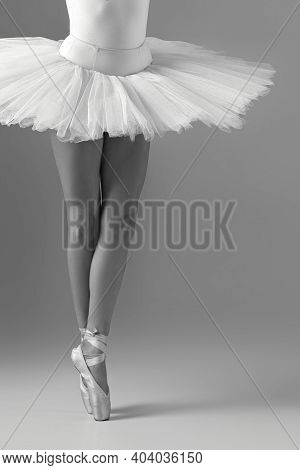 Legs Of A Ballerina In Pointe Shoes. Ballerina In White Tutu. Black And White Photo.