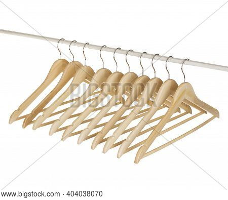 Close Up Of Wooden Cloth Hangers In Row Isolated On White Background.