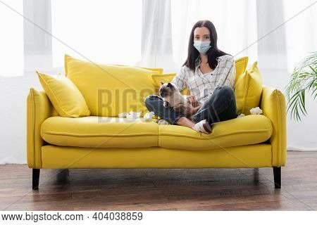 Allergic Woman In Medical Mask Looking At Camera While Sitting On Sofa With Cat Near Crumpled Paper