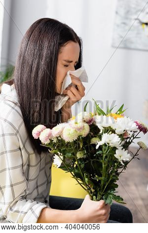 Allergic Woman Sneezing In Paper Napkin While Holding Flowers At Home