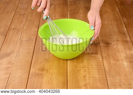 Women's Hands Mix Cake Ingredients In A Green Bowl.