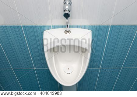 Toilet For Men. One Male Urinal With A Drain. Clean And Hygienic Mens Urination Room
