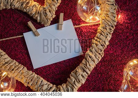 A Heart-shaped Frame With A Card On The Clothespins With A Place To Be Written On A Crimson Backgrou