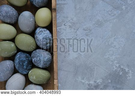 Easter Holiday. Gray, Blue And Green Marbled Easter Eggs In Wooden Tray On Gray Concrete Background.