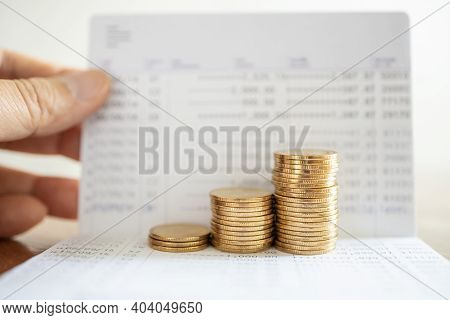 Money Saving And Financial Concept. Closeup Of Stack Of Gold Coins On Bank Passbook With Man Hand Ho