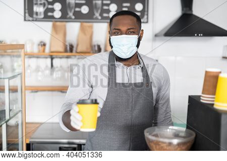 New Protective Rules During Quarantine Lockdown Period. An African-american Waiter Giving Cup Of Cof