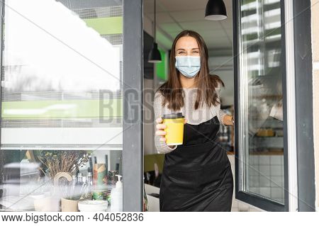 A Friendly Waitress Wearing Mask And Gloves Giving A Paper Cup Of Hot Coffee To A Customer Through A