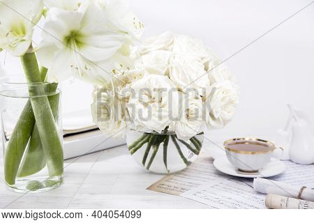 White Roses, Lily, In Round Vases With Two Cups Of Coffee On The Table For A Special Occasion As A K