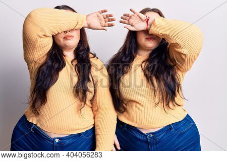 Young plus size twins wearing casual clothes covering eyes with arm, looking serious and sad. sightless, hiding and rejection concept