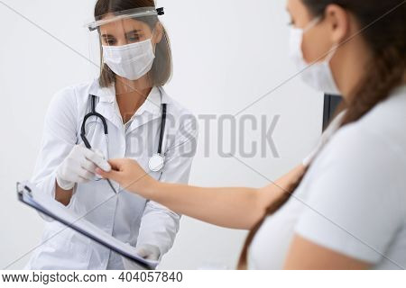 Pregnant Woman Signing Documents On Clipboard That Holding Gynecologist In Hands. Patient And Doctor