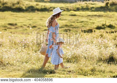 Young Mother Walking With Her Little Daughter In The Green Field. Family Holiday In Garden. Portrait